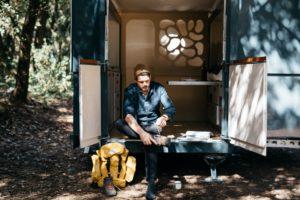 man sitting on edge of tiny house on wheels